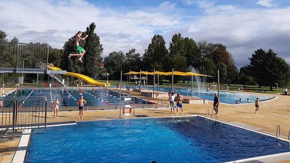 Badegäste im Freibad Mühlhausen. Ein Junge springt gerade vom Sprungturm.