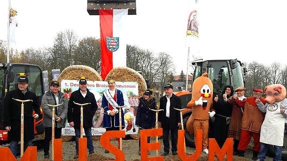 Elf Personen mit Bratwurst-Mützen oder verkleidet als Bratwurst und Schwein stehen nebeneinander.
