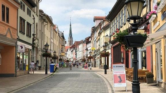 Eine Straßenszene mit Fußgängerzone und Geschäften
