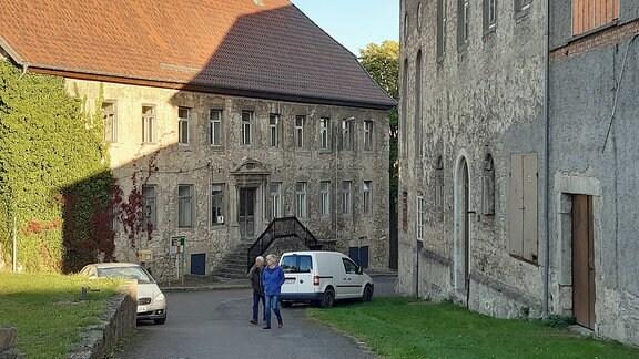 Vor zwei alten Gebäuden stehen zwei Autos und laufen zwei Menschen.