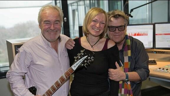 Die Musiker Jürgen Olsen und Nils Olsen stehen zusammen mit MDR THÜRINGEN-Moderatorin Sina Waage im Studio.