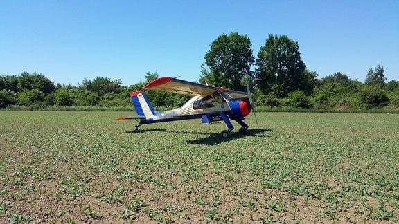 Ein Kleinflugzeug steht auf einem Acker.