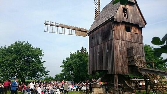Menschen sitzen vor einer großen Holzwindmühle