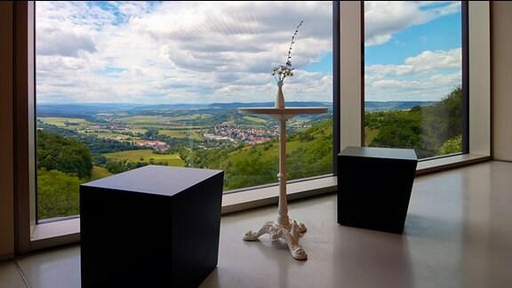 Ein Tisch mit einer Vase steht vor dem Fenster des Besucherzentrums auf der Leuchtenburg bei Kahla, durch das Fenster sieht man ein Tal mit mehreren Orten