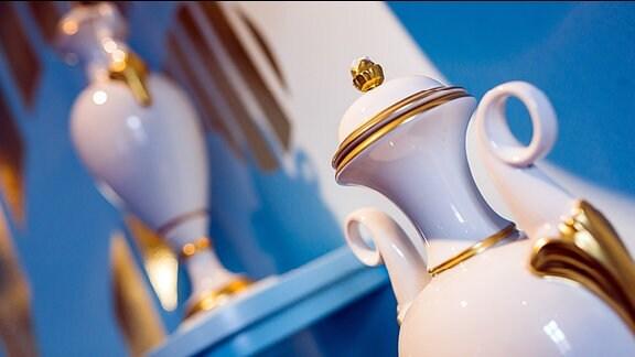 Eine kostbare Porzellankanne mit Goldrändern und ihr Spiegelbild.