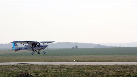 Auf einer Startbahn hebt ein Kleinflugzeug ab.