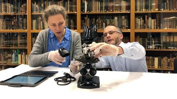 Museumsmitarbeiterin Dr. Ulrike Lötzsch und Gründungsdirektor Professor Timo Mappes begutachten ein L-Stativ-Mikroskop von Zeiss.