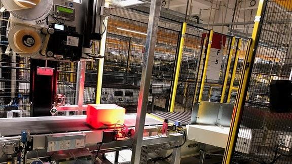 Auf einem Transportband werden die Amazon-Pakete im Logistikzentrum Gera gescannt.