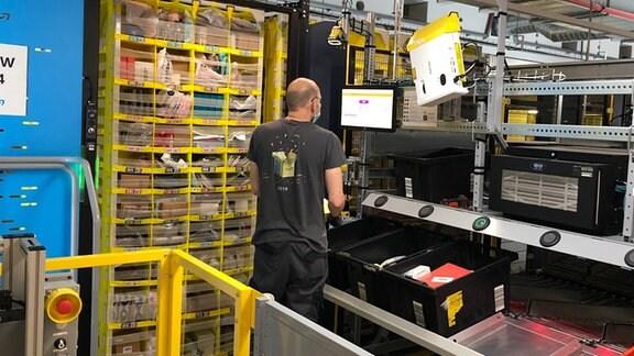 Die Mitarbeiter im Amazon-Logistikzentrum Gera nehmen die Ware aus kleinen gelben Regalen.