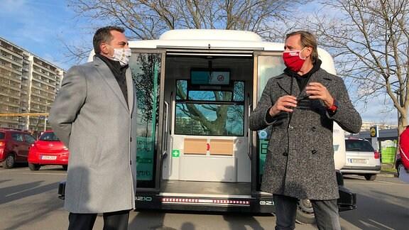 Zwei Männer mit Mundschutzmaske stehen vor dem modernen Kleinbus in Gera.