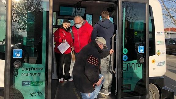 Menschen steigen aus einem modernen Kleinbus in Gera.