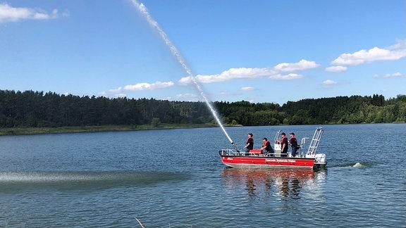 Auf einem Boot der Freiwilligen Feuerwehr Zeulenroda vom Typ RTB2 stehen Feuerwehrleute, sie schießen einen Wasserstrahl über die Talsperre.