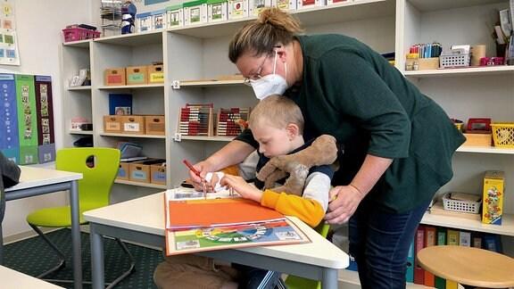 Eine Lehrerin erklärt einem Schüler in der Förderschule Schleiz eine Aufgabe.