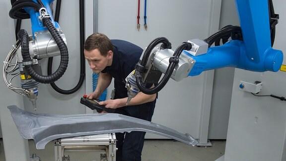 Ein Mann arbeitet an einer Lasermaschine zur Herstellung von Autoteilen.