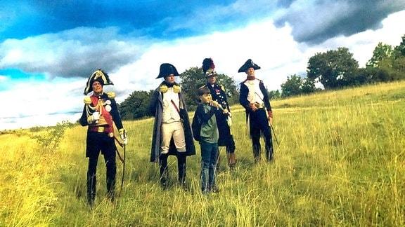 Ein Junge steht vor vier Männern in Unformen.