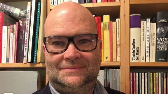 Mann mit Brille vor Bücherregal