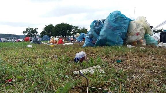 Mehrere übervolle Müllsäcke stehen auf einer Wiese