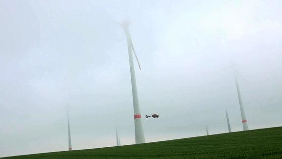 Ein Hubschrauber fliegt im Nebel durch eine Windkraftanlage.
