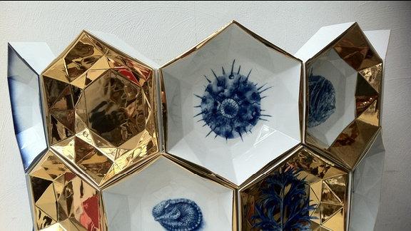 Teil einer aus blau und golden bemalten Porzellan-Waben zusammengesetzten Vase