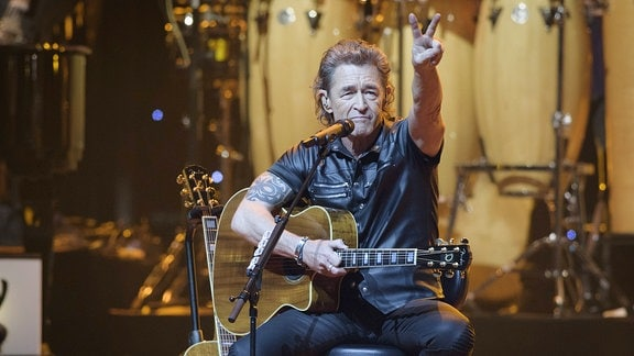 Peter Maffay sitzt mit der Gitarre auf der Bühne und macht ein Peace-Zeichen.