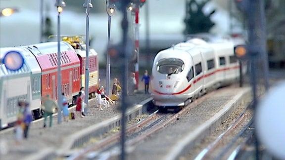 Modelleisenbahn fährt in einen Bahnhof ein. Modellfiguren stehen am Bahnsteig.
