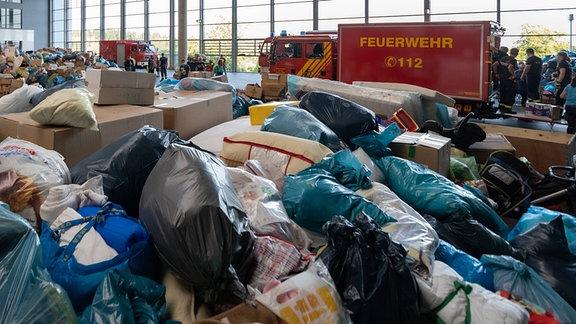 Feuerwehren aus verschiedenen Regionen Deutschlands laden die bereitgestellten Spenden in ihre LKW.