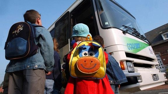 Kinder mit Ranzen stehen vor einem Schulbus