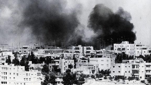 Rauchwolken nach Bombenexplosionen über der Stadt Amman. Schwarzweißfoto.