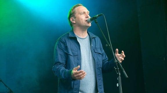 Thees Uhlmann singt in ein Mikrofon.