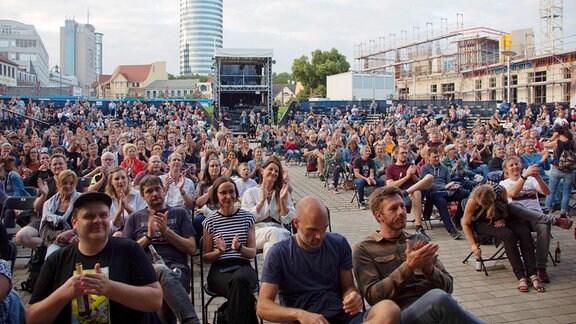 Zahlreiche Menschen sitzen auf Stühlen und applaudieren in der Kulturarena Jena.