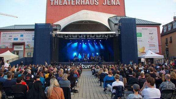 Blick aus dem Publikum auf eine blau beleuchtete Bühne, auf der Menschen musizieren