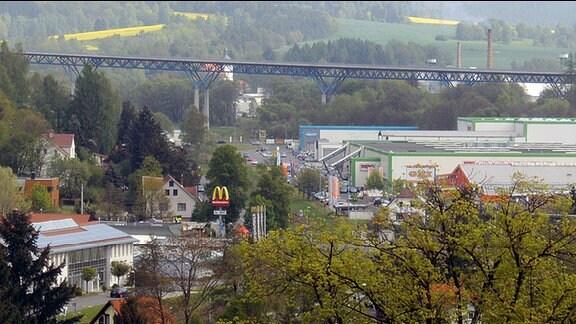 Hinter einem Industriegebiet ist eine Talbrücke einer Autobahnbrücke vor bewaldeten Hügeln zu sehen