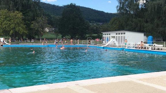 Schwimmbecken mit Wasserrutschen und Sitzmöglichkeiten sowie Liegeflächen.