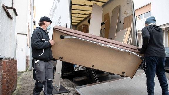 Möbelpacker beim beladen eines Lkw.