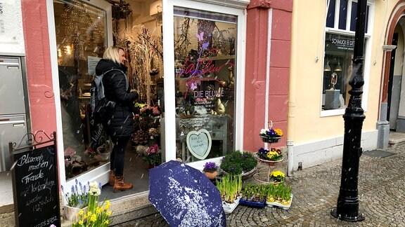 Eine Kundin betritt einen Blumenladen.