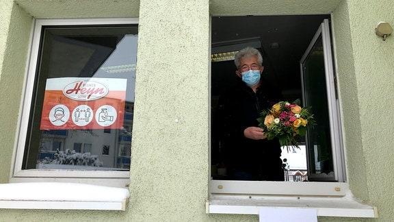 Walter Heyn gibt durch ein Fenster einen Blumenstrauß heraus.
