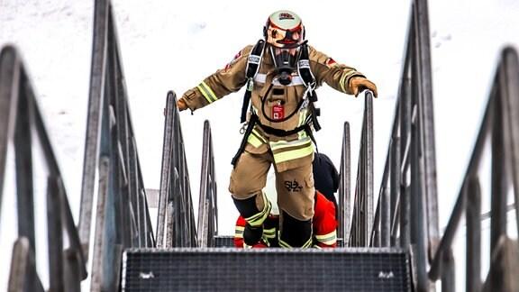 Ein Feuerwehrmann läuft in Schutzausrüstung eine Treppe hoch.