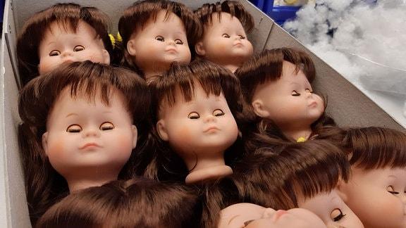 Puppenköpfe in einem Karton.