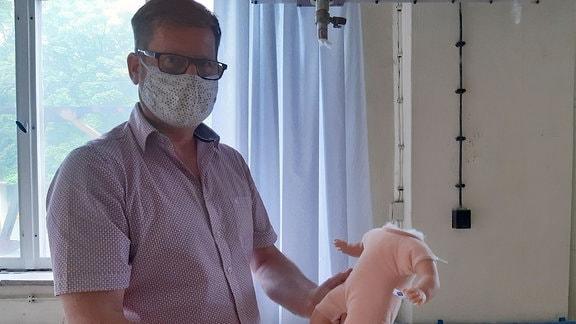 Ein Mann zeigt einen Puppenkörper ohne Kopf.