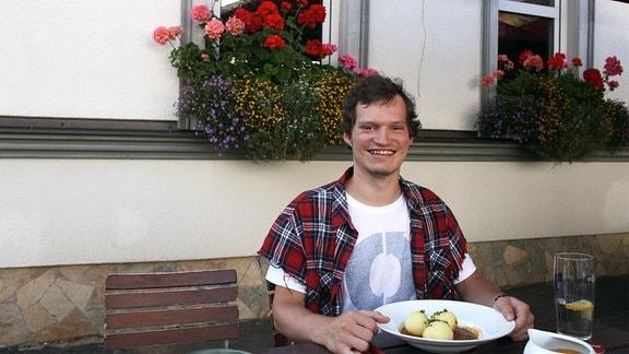 Ein Mann sitzt an einem Tisch vor einem Teller Klöße