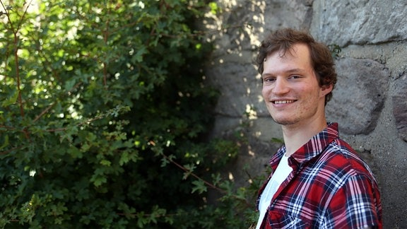 Ein Mann steht vor einer Mauer und blickt in die Kamera