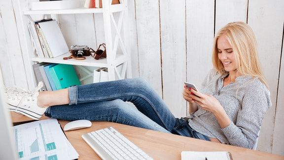 Eine junge Frau legt die Beine auf den Schreibtisch und schaut auf ihr Smartphone.