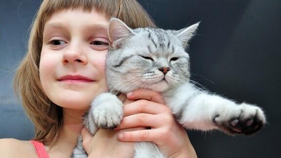 Mädchen drückt sich eine Katze ans Gesicht