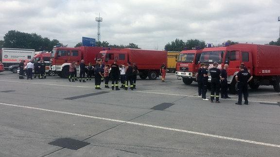 Menschen stehen vor Feuerwehrautos.