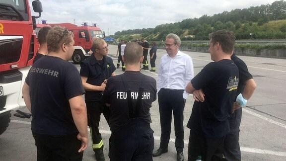 Thüringens Innenminister Georg Maier spricht mit Feuerwehrleuten.