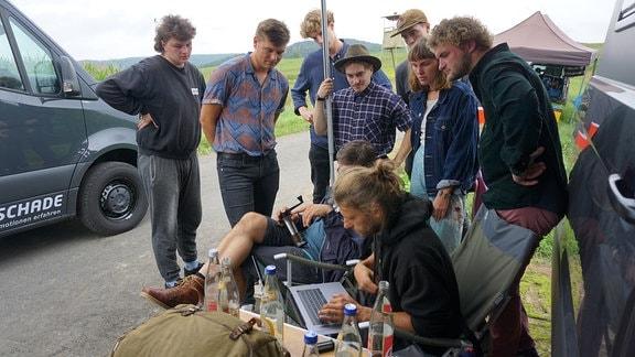 Eine Gruppe junger Menschen schaut auf einen Monitor an einem Feldrand