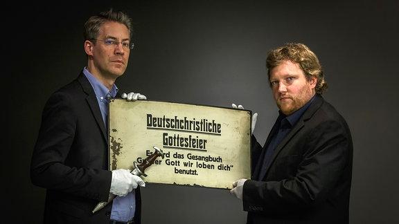 Zwei Männer halten mit weißen Handschuhen ein Schild mit der Aufschrift: Deutschchristliche Gottesfeier.