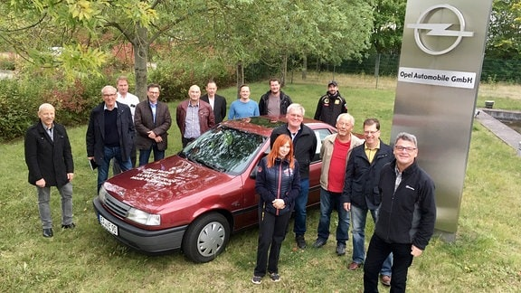 Menschengruppe steht um einen weinroten Opel Vectra.