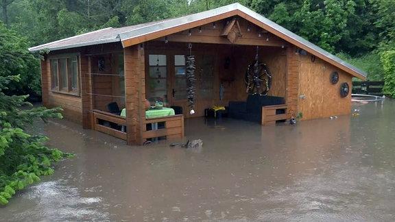 Ein Gartenhaus steht völlig unter Wasser.