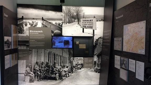 An den Wänden eines Raumes hängen großformatige Fotos.